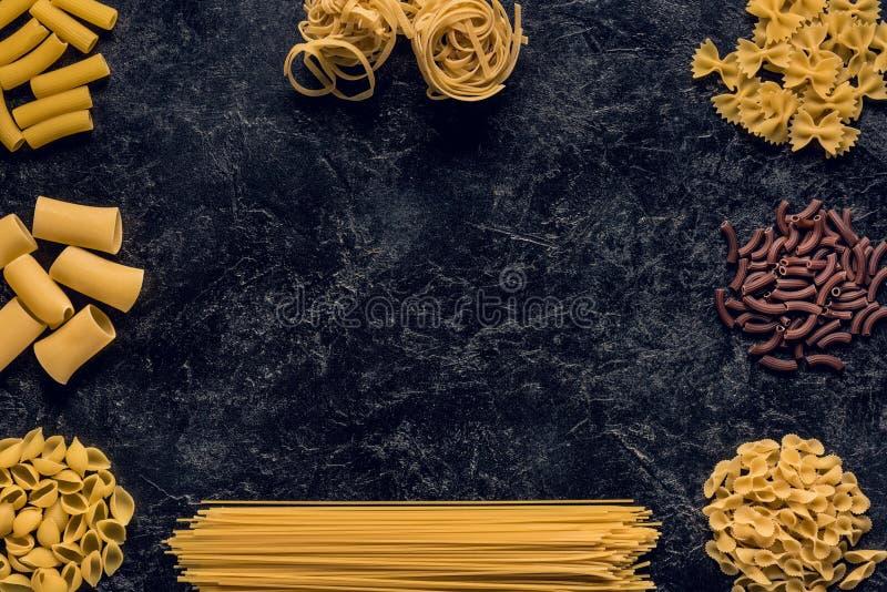 odgórnego widoku skład różnorodny surowy makaron na czerni obraz stock