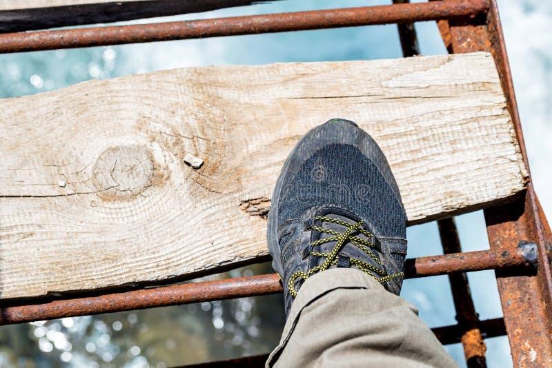 Odgórnego widoku stopa w wycieczkować but na drewnianym moście nad rzeką fotografia stock