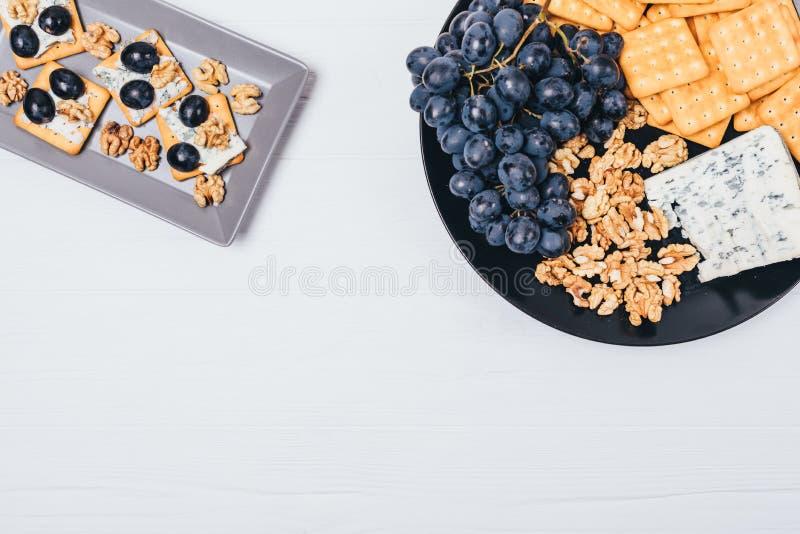 Odgórnego widoku talerz z canape blisko składników: ser, winogrona, krakersy i dokrętki, Mieszkanie przekąski nieatutowy karmowy  obraz stock