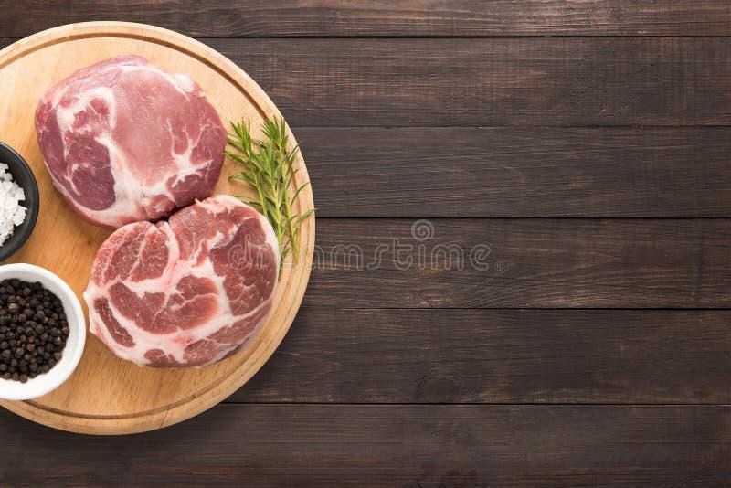 Odgórnego widoku wieprzowiny kotlecika surowy stek i czosnek, pieprz na drewnianym backgr obraz stock