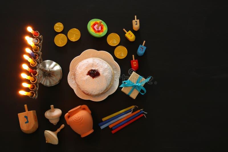 Odgórnego widoku wizerunek żydowski wakacyjny Hanukkah tło z tradycyjnym spinnig wierzchołkiem, menorah & x28; tradycyjny candela obraz stock