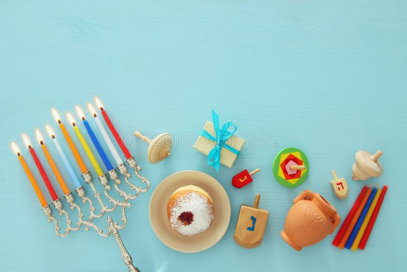 Odgórnego widoku wizerunek żydowski wakacyjny Hanukkah tło z tradycyjnym spinnig wierzchołkiem, menorah & x28; tradycyjny candela fotografia stock