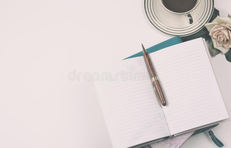 Odgórnego widoku wizerunek otwarty notatnik z pustymi stronami obok różanego i filiżanka kawy na czystym biurowym biurku Dla sumu zdjęcia royalty free