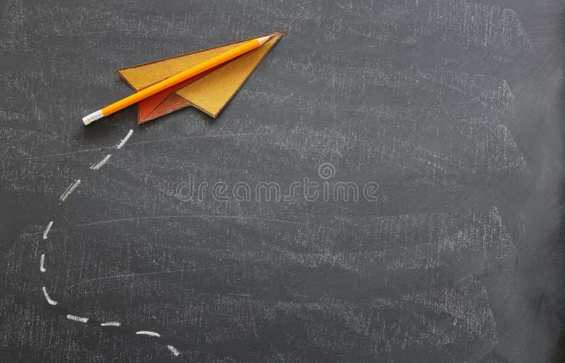 Odgórnego widoku wizerunek papieru ołówek nad sala lekcyjnej blackboard tłem i samolot zdjęcie stock