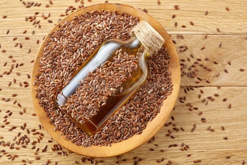 Odgórnego widoku zbliżenia obrazka lna ziarna i linseed olej w szklanej butelce na drewnianym tle, płytka głębia pole obraz royalty free