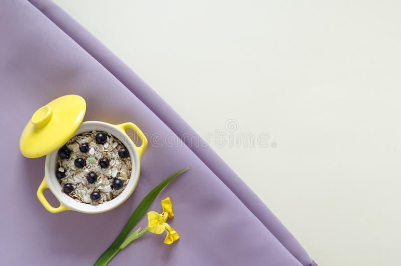 Odgórnego widoku zdrowa śniadaniowa żółta owsianka, muesli z świeżymi czarnymi jagodami i rodzynki, obraz royalty free