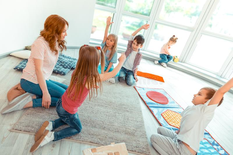 Odgórny widok ładni ładni dzieciaki podnosi ich ręki obrazy stock