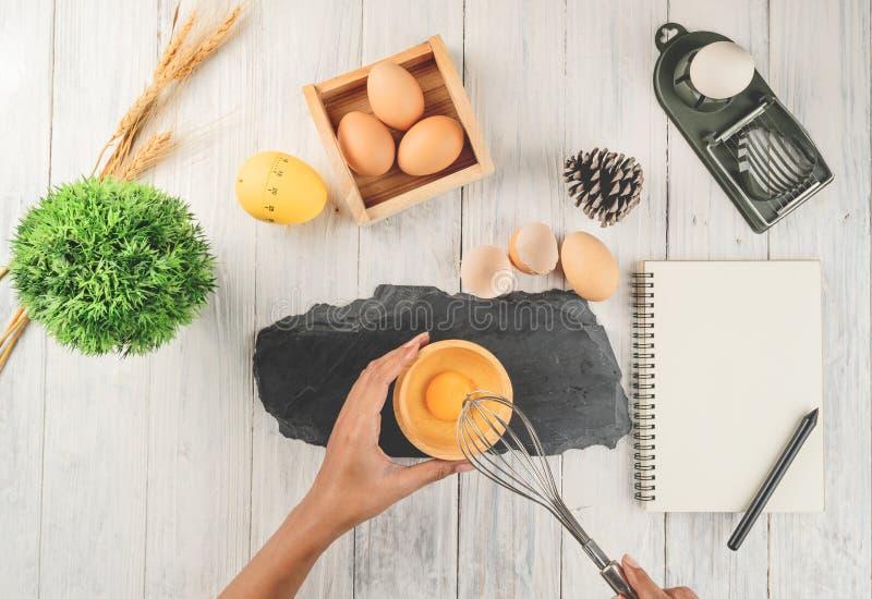 Odgórny widok łama jajko w drewnianego puchar kobieta szef kuchni Femal fotografia stock
