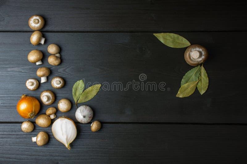 Odgórny widok świeże pieczarki i cebula z podpalanym liściem na zmroku wo obrazy stock