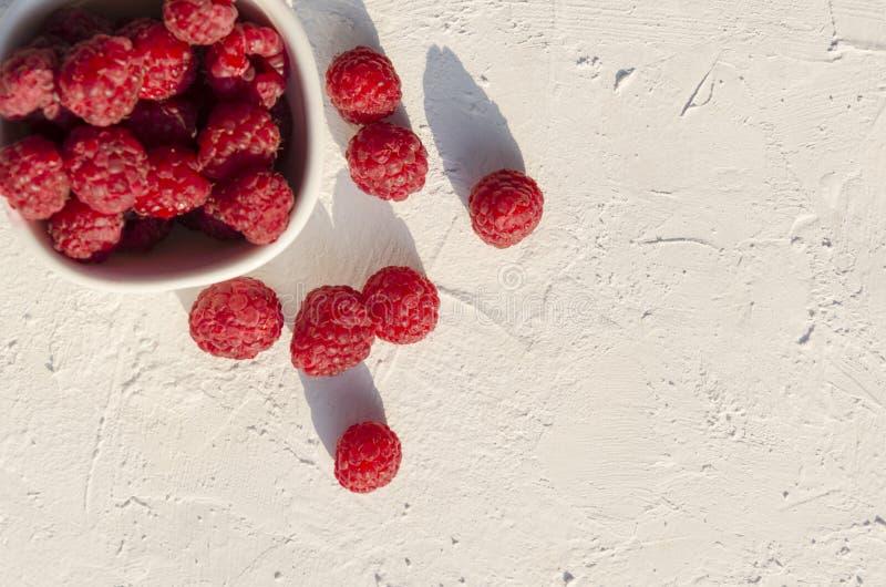 Odgórny widok świezi wyśmienicie rasberries na białym stole, opróżnia przestrzeń dla teksta Ranek przek?ska Naturalne ?wiat?o w r fotografia stock