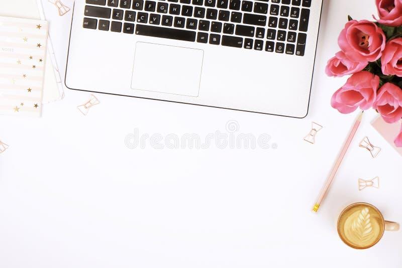 Odgórny widok żeńskiego pracownika desktop z laptopem, kwiatami i różnymi biurowych dostaw rzeczami, Kobiecy kreatywnie projekta  obrazy stock
