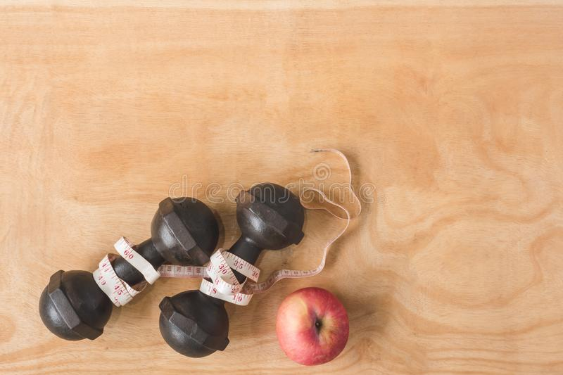 Odgórny widok żelazni dumbbells z miarą taśmy i jabłko na stole zdjęcie stock