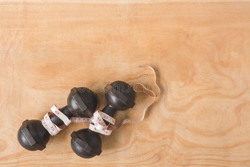 Odgórny widok żelazni dumbbells z miarą taśmy na drewnianym stole obrazy royalty free