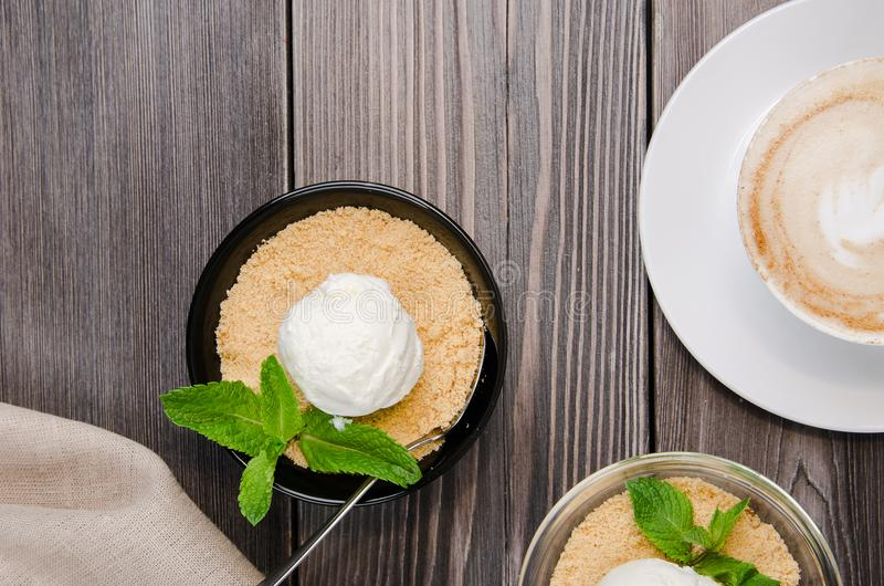 Odgórny widok Apple rozdrobni deser z waniliowym lody, zieleni mennica na popielatym drewnianym stole Filiżanki kawy cappuccino z obraz royalty free