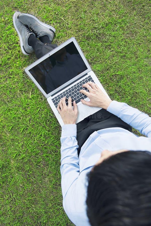 Odgórny widok azjatykci biznesmen używa laptop dla pracy obraz stock