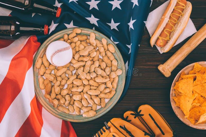 odgórny widok baseball piłka na talerzu z arachidami, kijem bejsbolowym, rękawiczką, hot dog i piwnymi butelkami, obraz royalty free