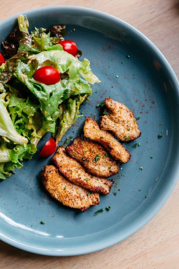 Odgórny widok BBQ piec na grillu kurczak pierś z sałatką słuzyć w błękita talerzu na drewnianym stole obraz royalty free