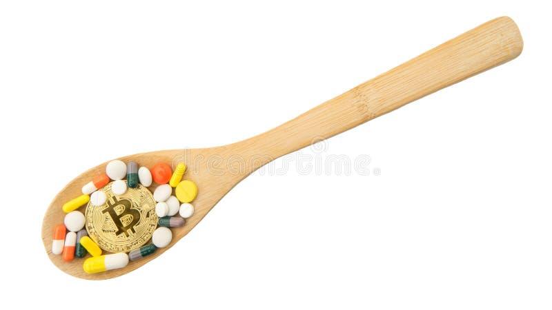 Odgórny widok bitcoin, asortowane farmaceutyczne medycyn pigułki, pastylki na drewnianej łyżce odizolowywającej na białym tle fotografia stock