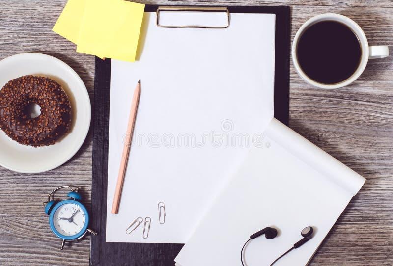 Odgórny widok biuro accessorise na drewnianym desktop: zegaru, filiżanki kawy, schowka, pączka, notepad i kleidła majchery, zdjęcia stock