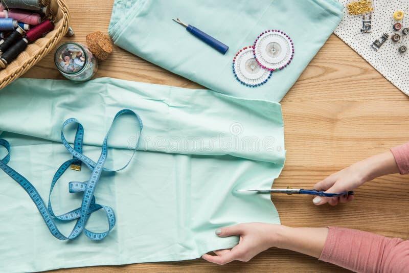 odgórny widok cropped kobieta wręcza tnącą tkaninę nożycami obrazy royalty free