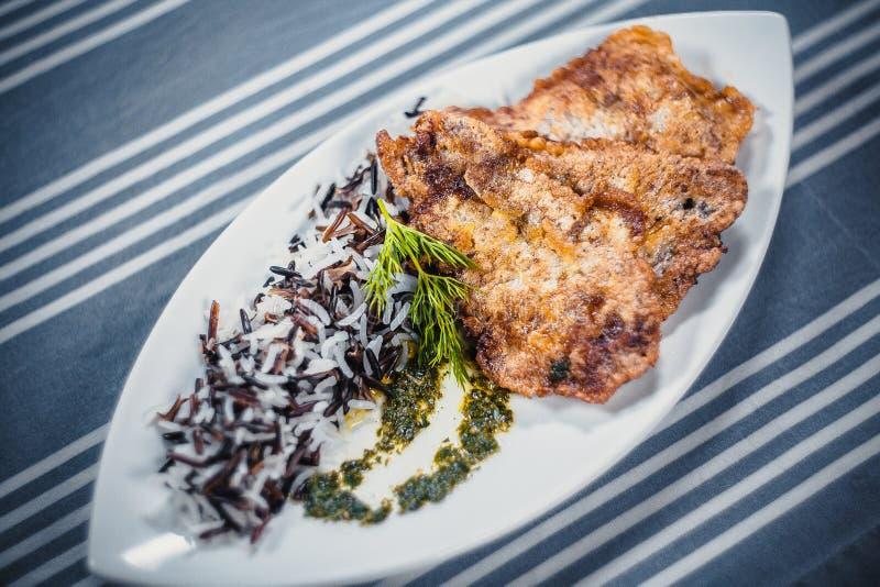 Odgórny widok cutlets od szczupaka z ryż na białym talerzu Talerz na stole z błękitnym tablecloth w białych paskach zdjęcie stock