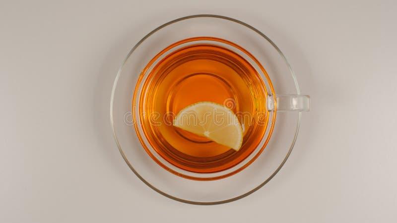ODGÓRNY widok: Cytryna plasterek pływa w czarnej herbacie w szklanej herbacianej filiżance z naczyniem zdjęcia stock