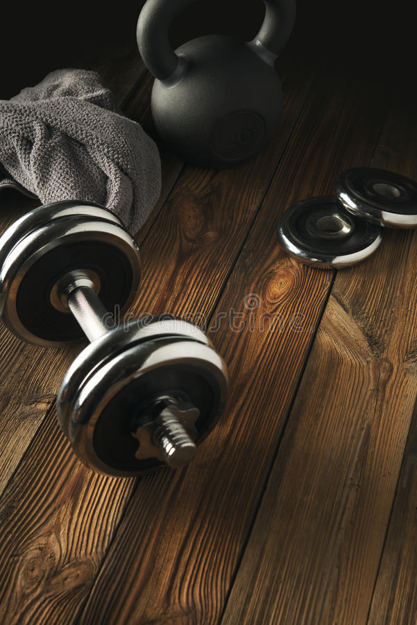 Odgórny widok czerni żelaza kettlebell, dumbbell i popielaty ręcznik na wo, zdjęcia stock