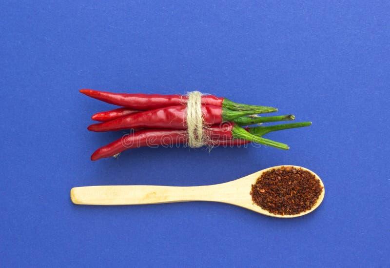 Odgórny widok, czerwonego chili pieprz wiążący z, warkoczem i drewnianą łyżką na błękitnym tle fotografia royalty free