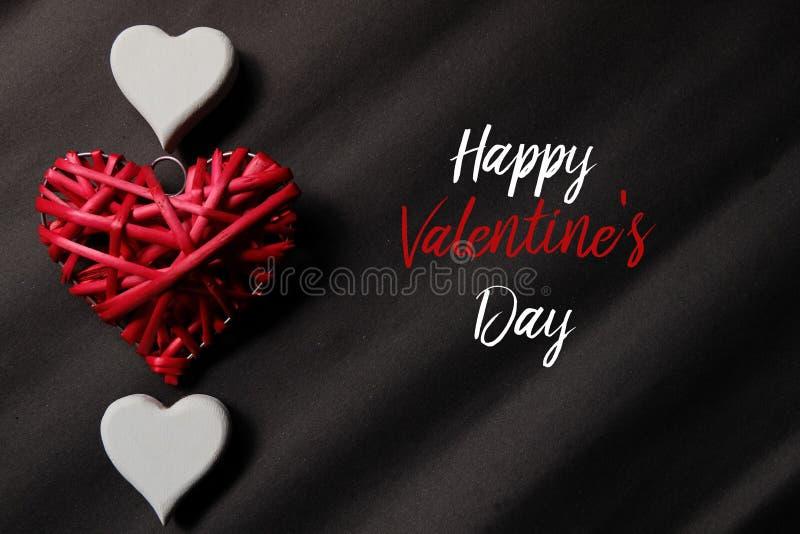 Odgórny widok czerwony i biały kierowy drewniany handcraft na czarnym tle pisać z Szczęśliwym Valentine& x27; s dzień obraz royalty free