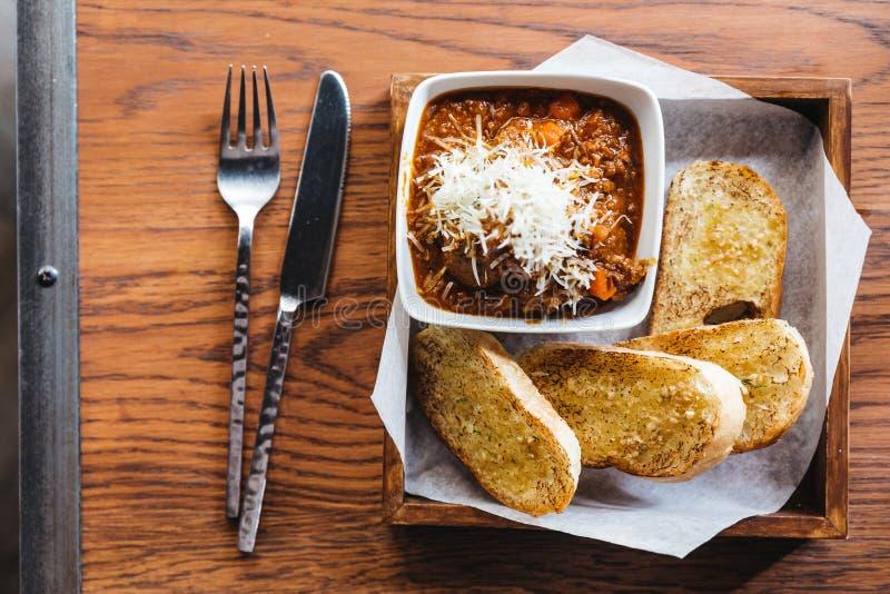 Odgórny widok czosnku chleb z mięsną kumberland polewą z mozzarella serem, Słuzyć na drewnianym pudełku z nożem i rozwidleniem obrazy stock
