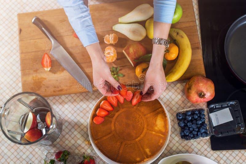 Odgórny widok dekoruje tortową warstwę z truskawką kobieta Gospodyni domowa kulinarny owocowy kulebiak obraz stock