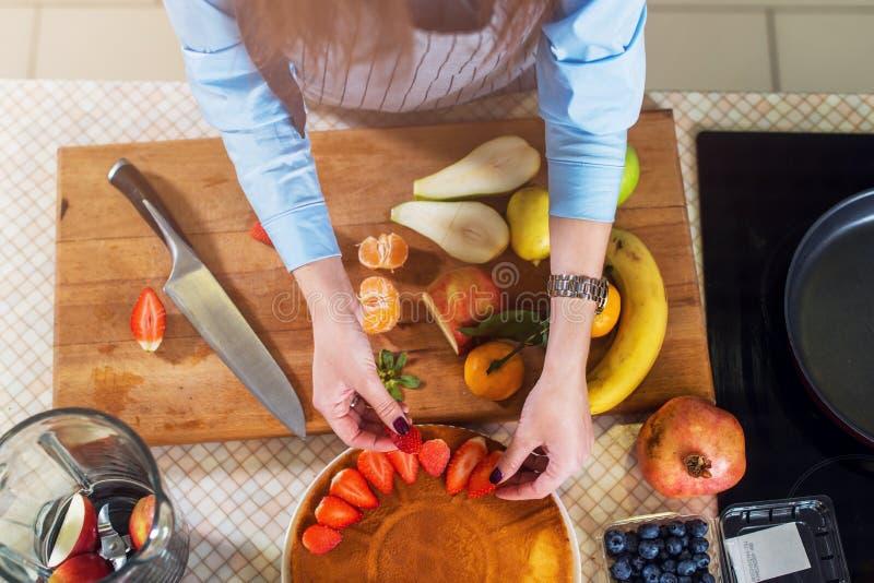 Odgórny widok dekoruje tortową warstwę z truskawką kobieta Gospodyni domowa kulinarny owocowy kulebiak fotografia stock