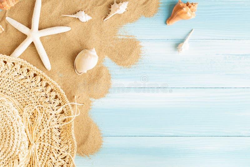 Odgórny widok denny słomiany kapelusz i morze łuska na dennym piasku na błękitnym drewnianym tle, lata pojęcie na pustej błękitne obrazy royalty free