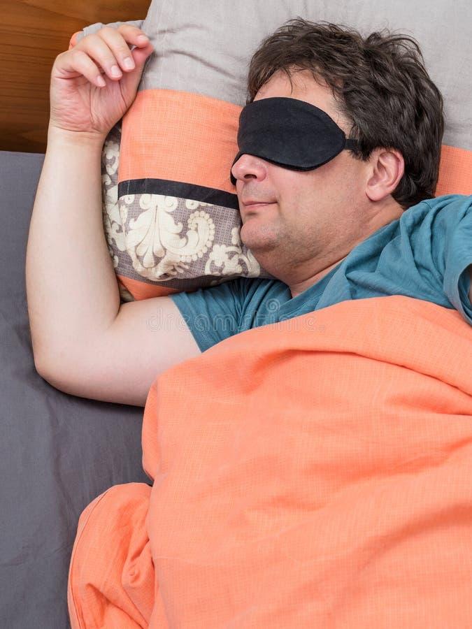Odgórny widok dojrzały mężczyzna w czerni masce śpi na łóżku obrazy stock