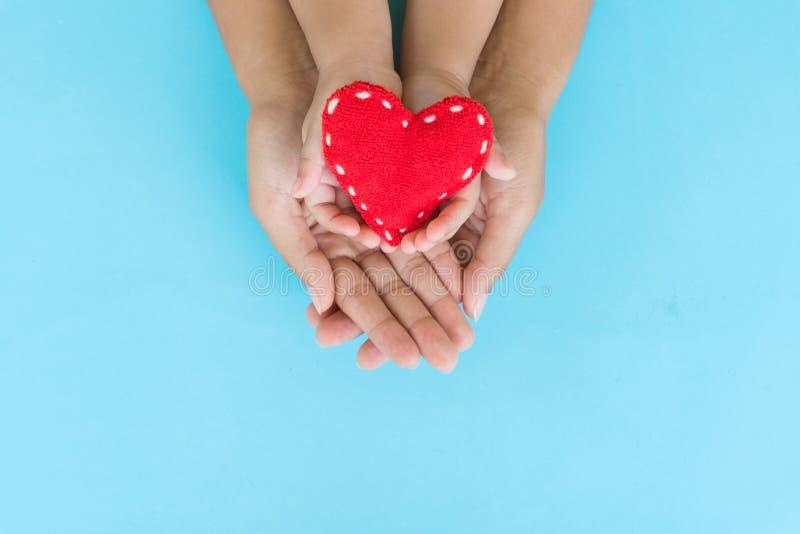 Odgórny widok dorosłego i dziecka mienia czerwony serce w rękach obrazy royalty free