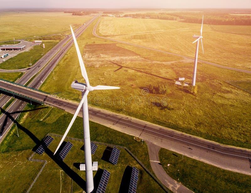 Odgórny widok drogowi przelotni pobliscy wiatrowi gospodarstwa rolne i panel słoneczny w środku zieleni pole zdjęcia royalty free