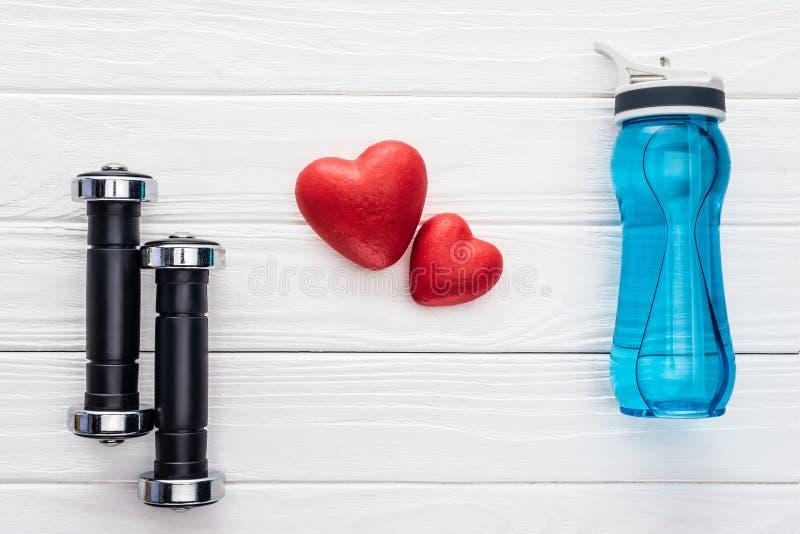 odgórny widok dumbbells, butelka wodni i czerwoni serca zdjęcie royalty free
