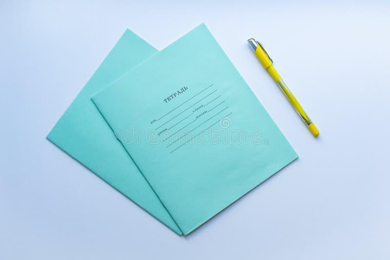Odgórny widok dwa ucznia zeszytu z żółtym piórem na białym tle Pojęcie edukacja, minimalizm obraz stock