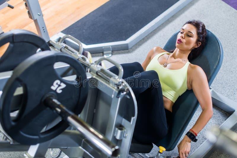 Odgórny widok dysponowana młoda kobieta robi nogi spotkanie z prasą gym fotografia stock