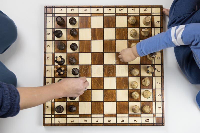 odgórny widok dziecko i dorosły bawić się szachy na białym backgr fotografia stock