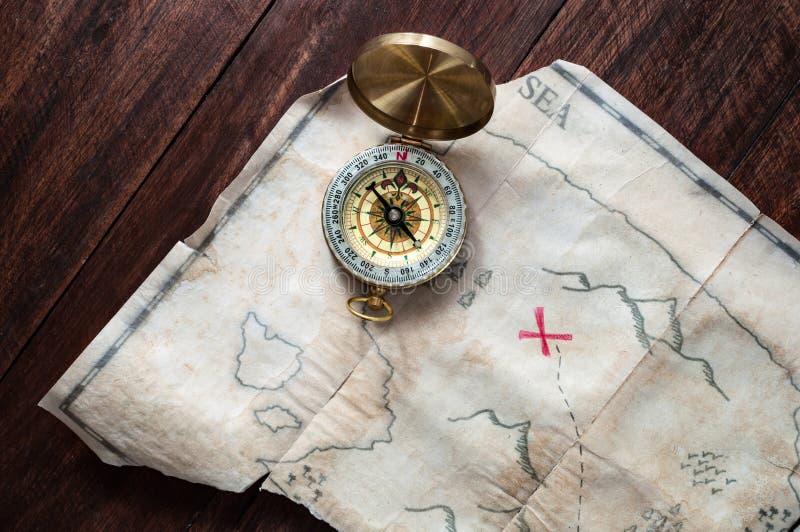 Odgórny widok fałszować pirata rocznika mapę skarb wyspa z czerwonym krzyżem na drewnianym stole zdjęcia stock