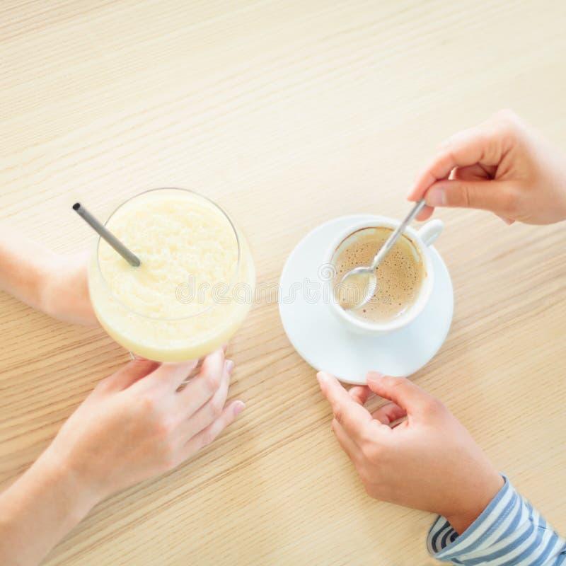 Odgórny widok femake ręki z napojami na drewnianym stole zdjęcia stock