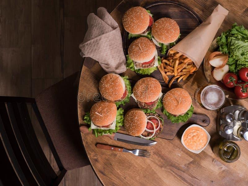 Odgórny widok hamburgery z wołowiny mięsem obok francuskich dłoniaków fotografia stock