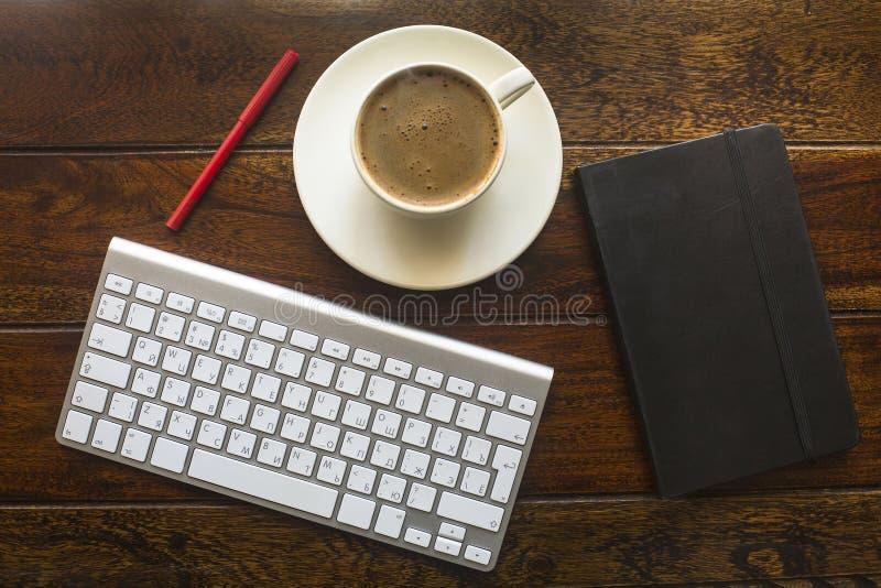 Odgórny widok klawiatura, ołówek, czarny notatnik i filiżanka kawy na drewnianym stole, zdjęcie royalty free