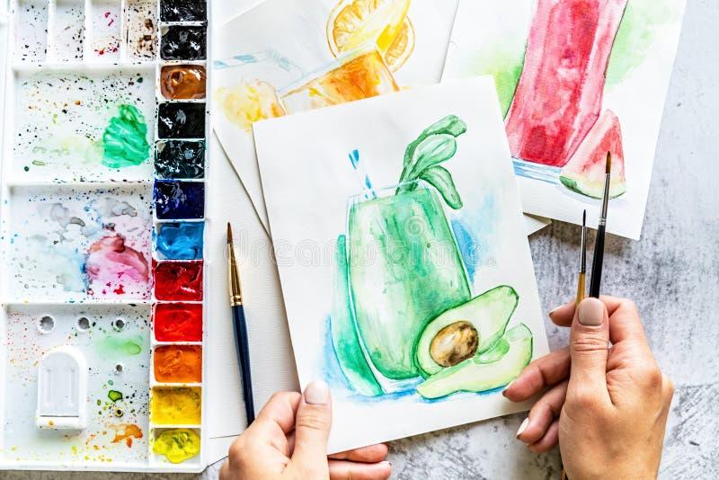 Odgórny widok kobiet ręki rysuje avocado smoothie z akwareli paintbrush na drewnianym stole i farbami ilustracji