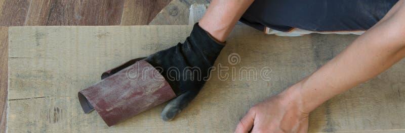 Odgórny widok kobieta wręcza piłować drewnianą deskę indoors Pojęcia - rzemiosło, carpentery, DIY obraz stock