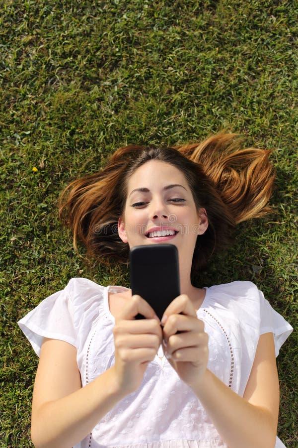 Odgórny widok kobiety lying on the beach na trawie texting na mądrze telefonie fotografia stock