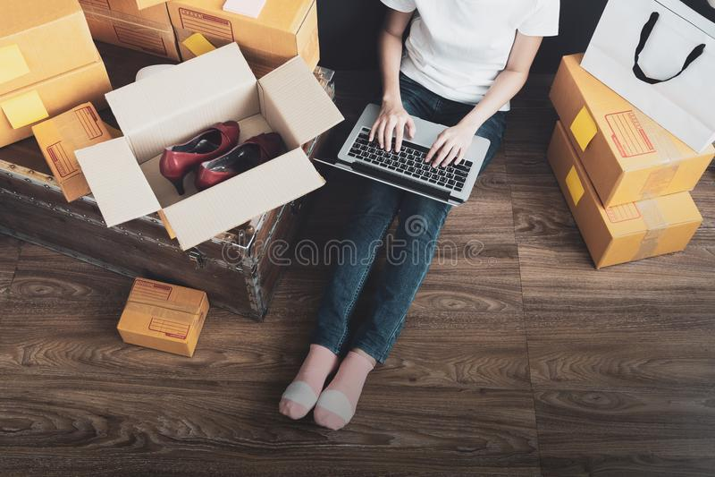 Odgórny widok kobiety pracuje laptop od domu na drewnianej podłoga z pocztowym pakuneczkiem, Sprzedaje online pomysłu pojęcie zdjęcia royalty free