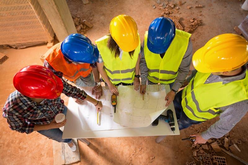 Odgórny widok kolorowi ciężcy kapelusze architekci przy budową siedzi obraz stock