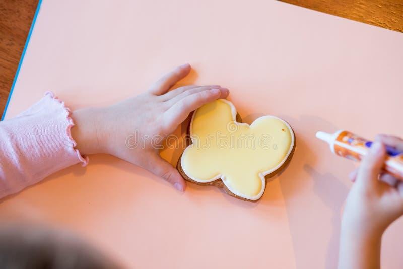 Odgórny widok, kolorowy handmade Easter protestuje, piekarnia, ciastka kłaść na stole i ręk pokazywać malujący, dekorujący mały obraz stock